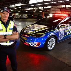 Victoria Police Inspector Stuart Bailey with the first all-electric vehicle in its operational fleet.